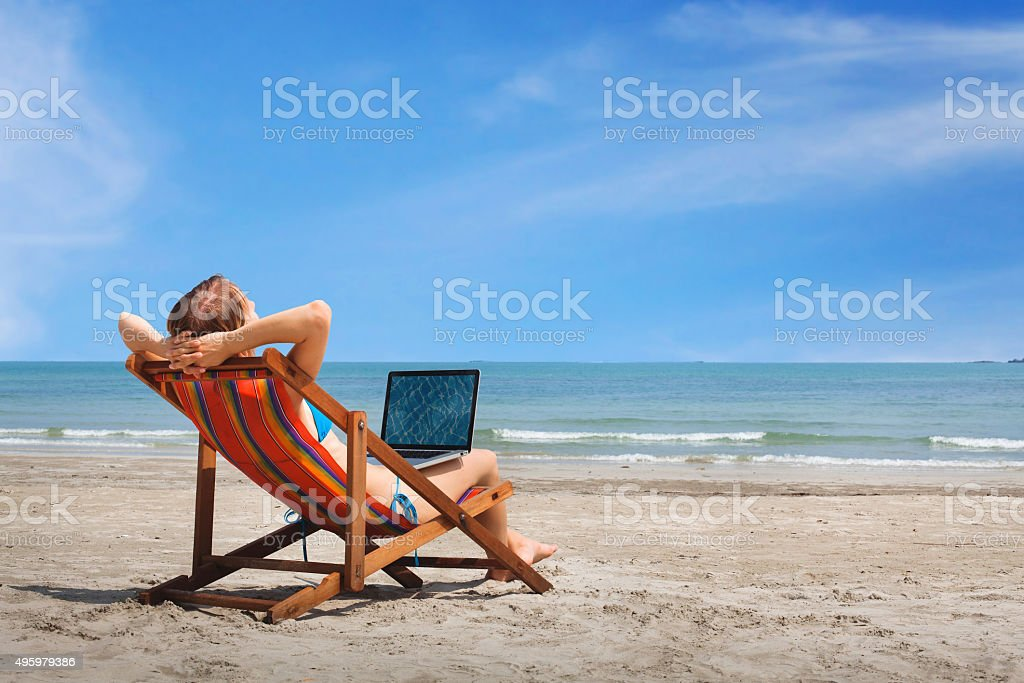 carefree woman with laptop on the beach stock photo