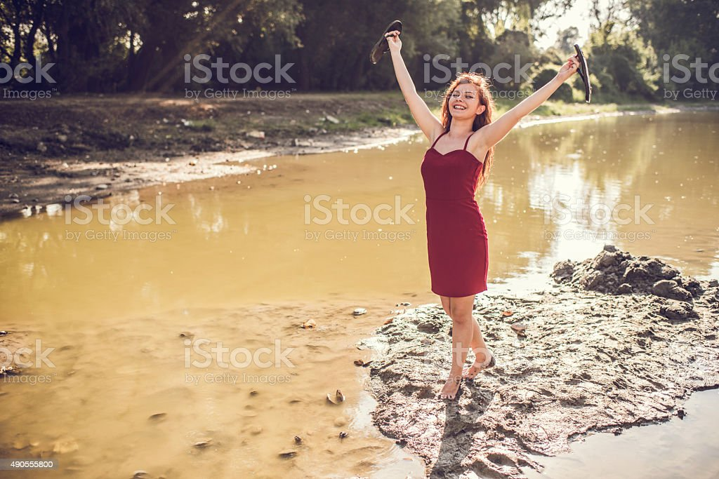 Carefree woman with raised arms in a mud. stock photo