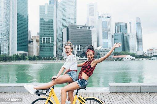 Side view of carefree girlfriends enjoying biking outdoors, having fun.