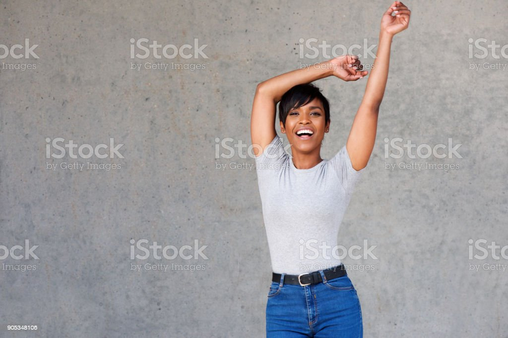 Carefree young african female model standing with arms raised stock photo
