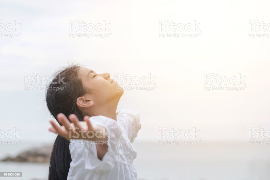 Carefree young Asian girl taking a deep breath natural bliss fresh air, opening arms relaxing on the beach at sea enjoying healthy living life quality during summer or spring break vacation stock photo