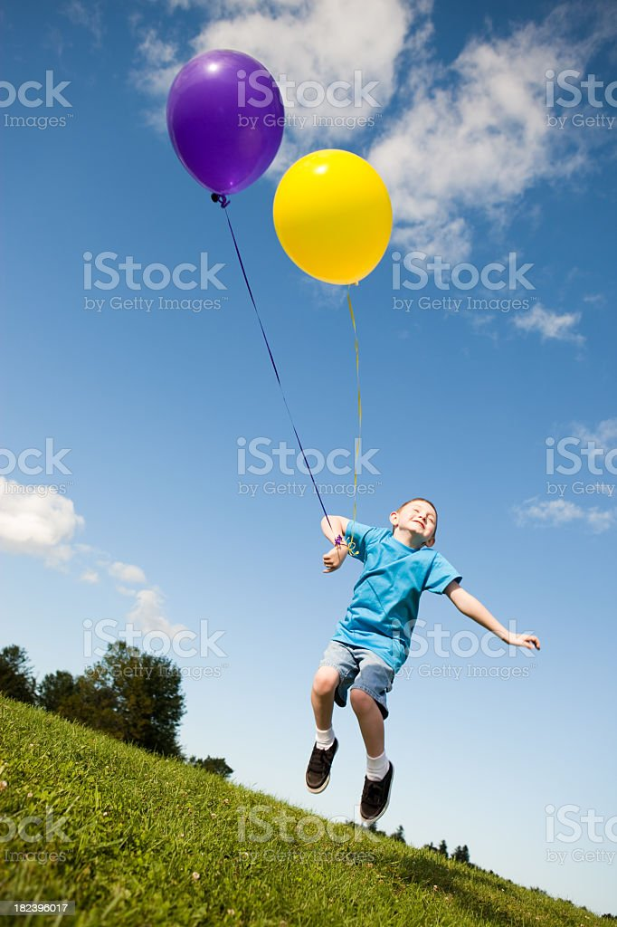 Carefree Young Boy Jumping with Balloons Outside royalty-free stock photo