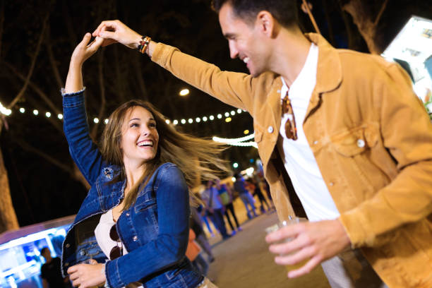 carefree young couple dancing holding hands in eat market in the street at night. - date night stock pictures, royalty-free photos & images