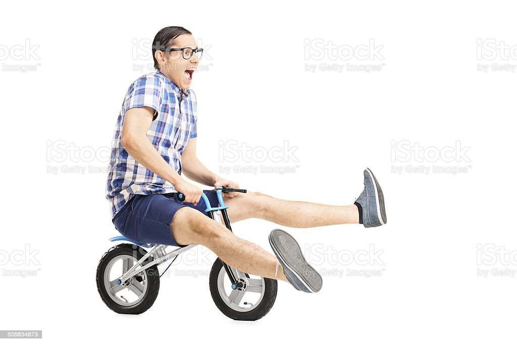 Carefree young guy riding a small bike stock photo