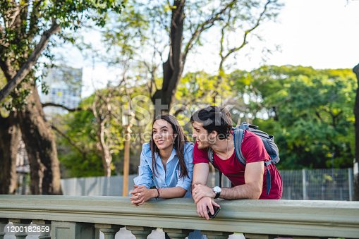 Close-up of relaxed Hispanic tourists in their 20s leaning on balustrade and enjoying time together in Buenos Aires.