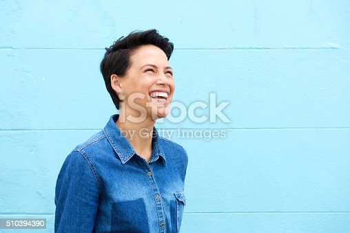 istock Carefree young woman laughing against blue background 510394390