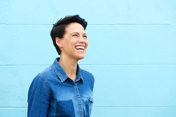 sem preocupações mulher jovem sorrindo contra fundo azul - lifestyle color background - fotografias e filmes do acervo