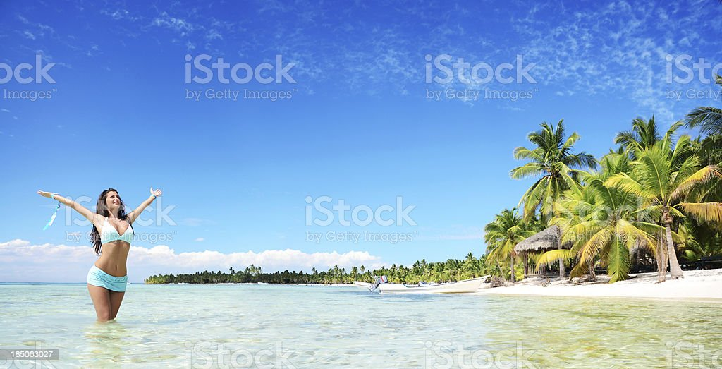 Carefree young woman relaxing on tropical beach panoramic stock photo
