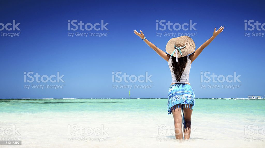 Carefree young woman relaxing on tropical beach stock photo