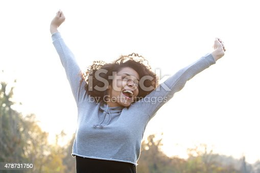 istock Carefree young woman smiling with arms raised 478731750