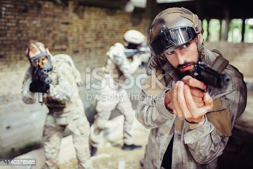 istock Careful and professional killers are taking aim in different directions. They are doing that calm but confident. There is a soldier's leader having pistol in hands. 1140378985