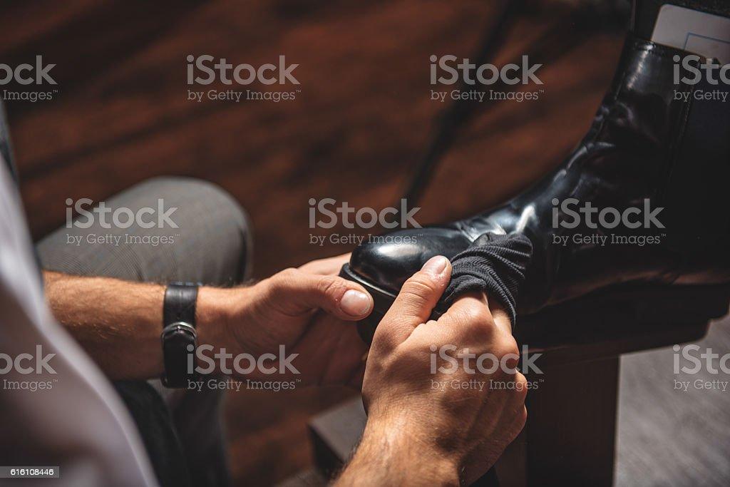 careful artisan taking care of shoes stock photo