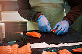 Careful cutting of salmon fish fillets preparation Valencia Spain