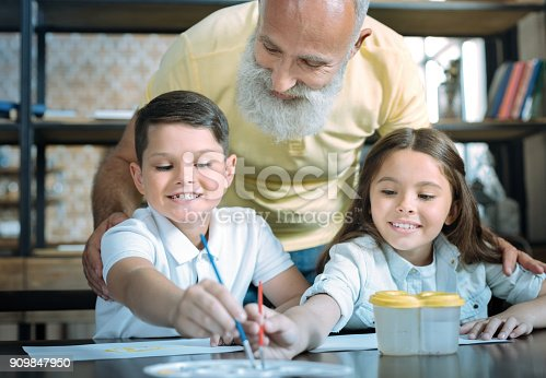 istock Careful grandfather looking at kids painting together 909847950