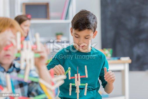 648947070 istock photo Careful Hispanic schoolboy makes something in art class 648946938