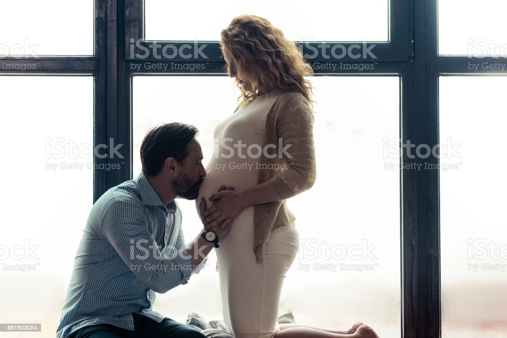 Careful husband kissing the belly of his wife stock photo