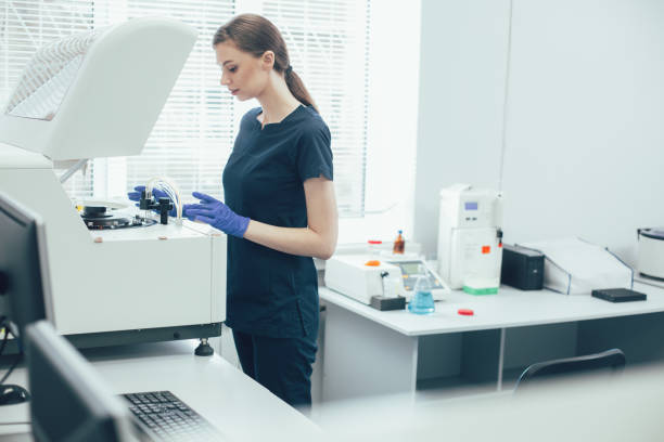Careful lab technician working with centrifuge machine stock photo stock photo