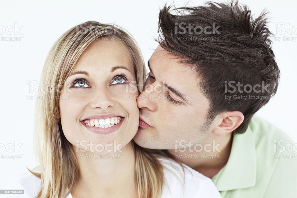 Careful man kissing his smiling girlfriend against a white background stock photo