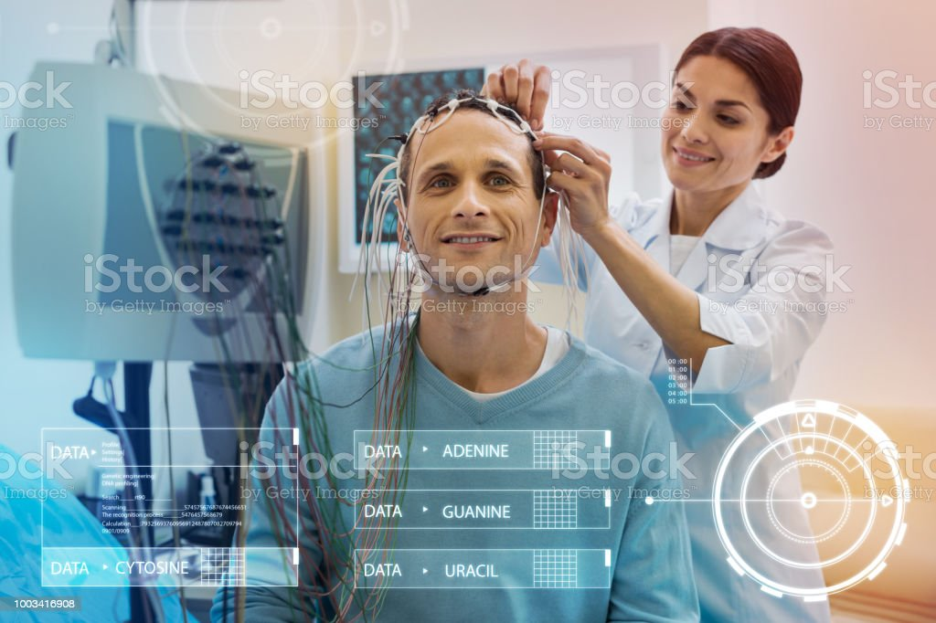 Careful nurse touching the wires while preparing her patient for EEG stock photo