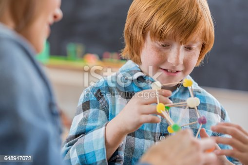 648947070 istock photo Careful schoolboy builds something in science class 648947072