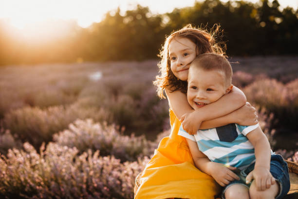 Careful sister embracing her small brother while posing against the sunshine with a lavender field on background stock photo