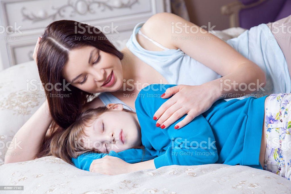 Careful young mother putting down her little daughter. stock photo