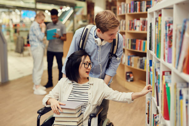 Careful young volunteer pushing wheelchair with Asian student girl while assisting her in library stock photo