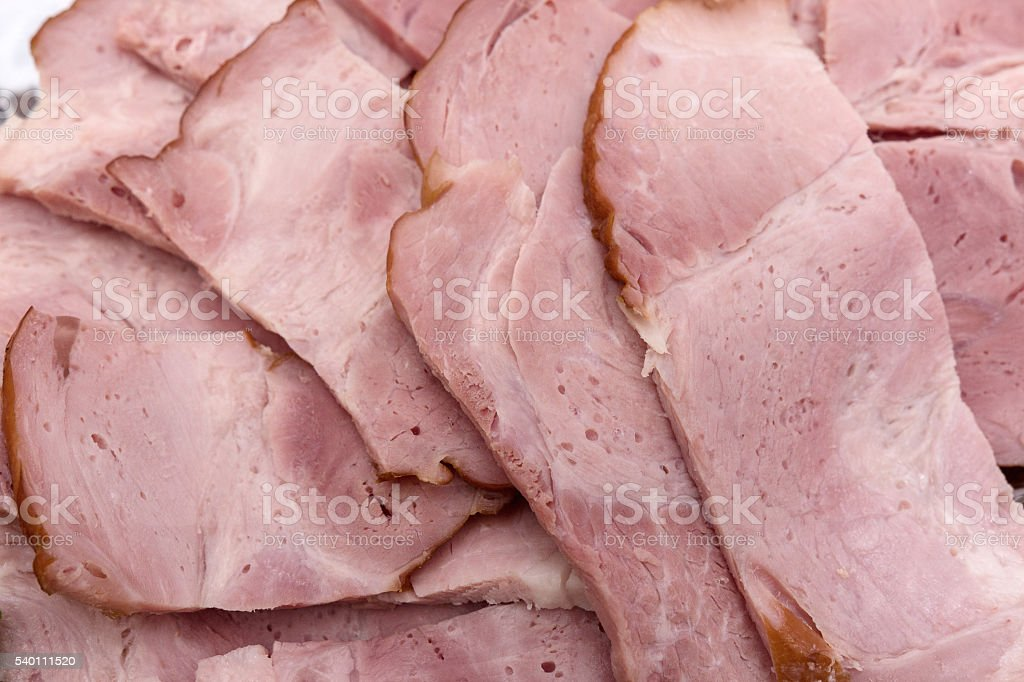 carefully cut into square pieces of ham stock photo