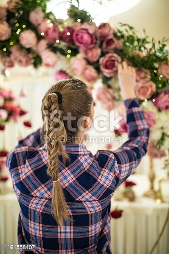 Unrecognizable woman working on beautiful floral wedding decoration, with pink and white roses at banquet hall