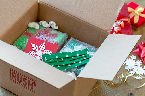 Carefully Wrapped Christmas Gifts Ready for Shipping in a Cardboard box marked Rush