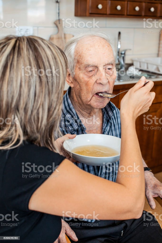 Caregiver and a Senior Man having Lunch stock photo