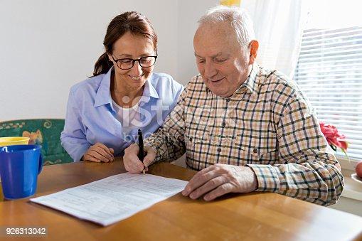 istock Caregiver and elderly man reading paperwork 926313042