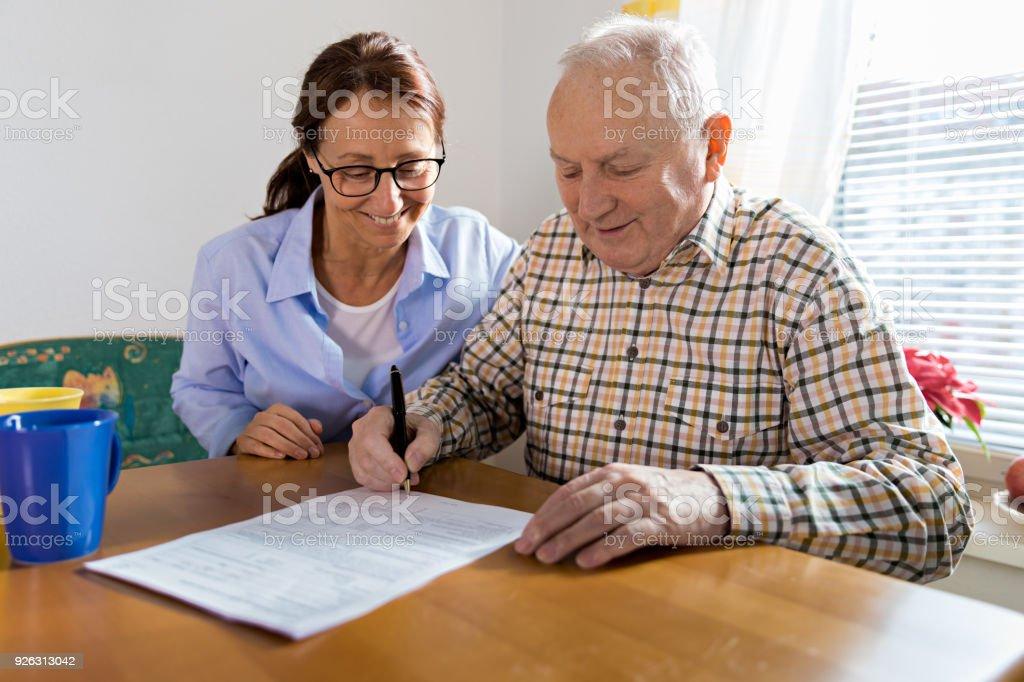 Caregiver and elderly man reading paperwork stock photo