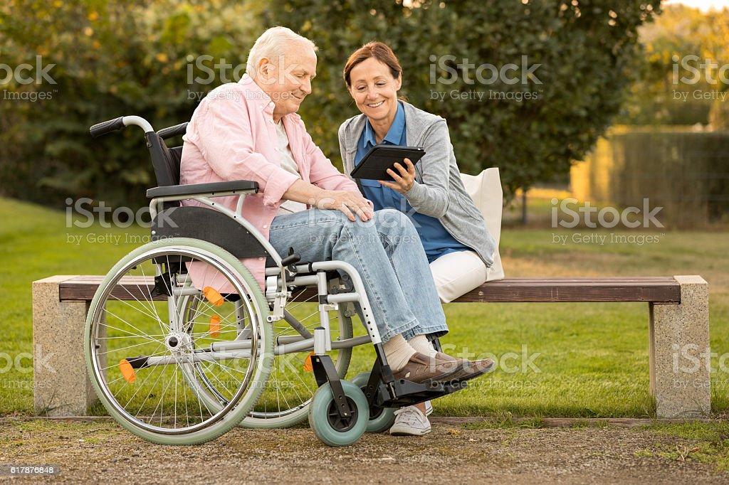 Caregiver and senior man on park bench, using digital tablet - foto de stock