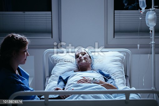 928968772 istock photo Caregiver and weak senior woman during treatment in the clinic 1013929374