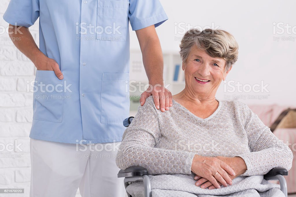 Caregiver and woman on wheelchair with hand on her shoulder photo libre de droits
