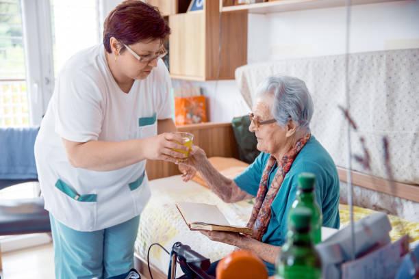 pflegeperson senior frau trinken bringen, in der alten mitte - jagdthema schlafzimmer stock-fotos und bilder