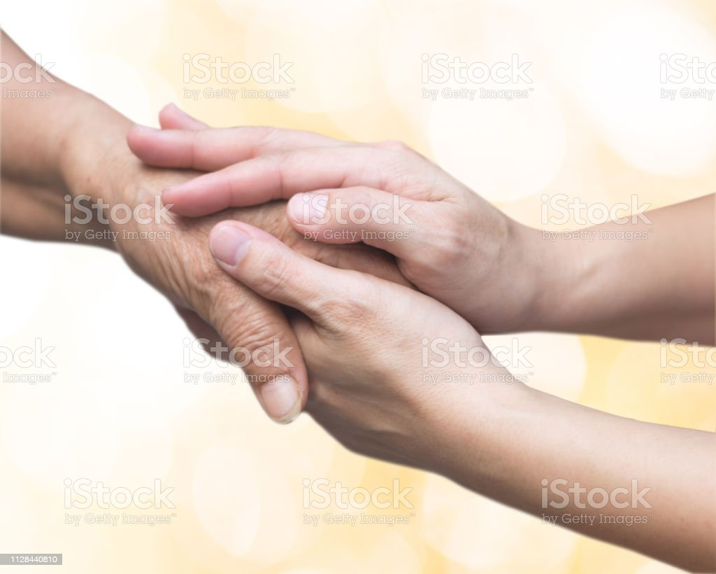 Caregiver, carer hand holding elder hand for hospice care. Philanthropy kindness to disabled old people concept with gold bokeh background.Happy mother's day. Caregiver, carer hand holding elder hand for hospice care. Philanthropy kindness to disabled old people concept with gold bokeh background.Happy mother's day. A Helping Hand Stock Photo