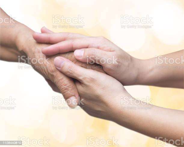 Caregiver Carer Hand Holding Elder Hand For Hospice Care Philanthropy Kindness To Disabled Old People Concept With Gold Bokeh Backgroundhappy Mothers Day Stock Photo - Download Image Now