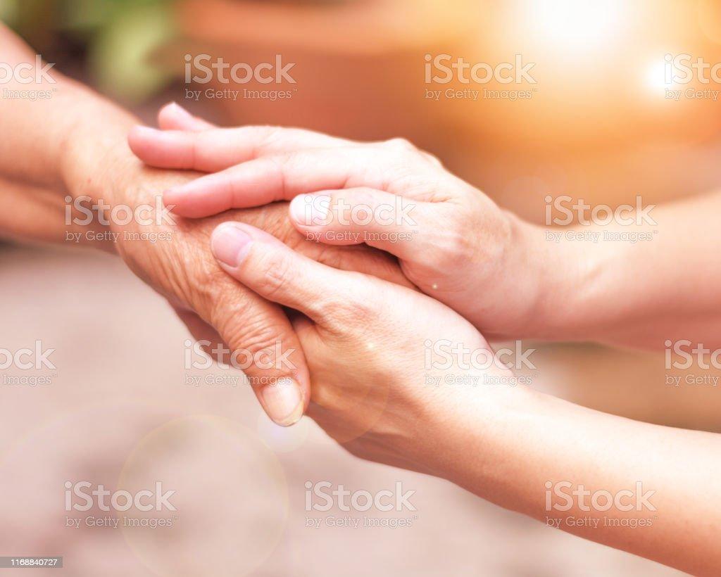 Vårdgivaren, CARER hand Holding Elder hand i hospice Care. Filantropi vänlighet till handikappade konceptet. - Royaltyfri Assistans Bildbanksbilder