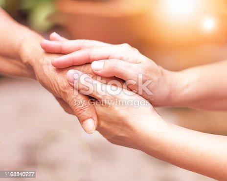 istock Caregiver, carer hand holding elder hand in hospice care. Philanthropy kindness to disabled concept. 1168840727