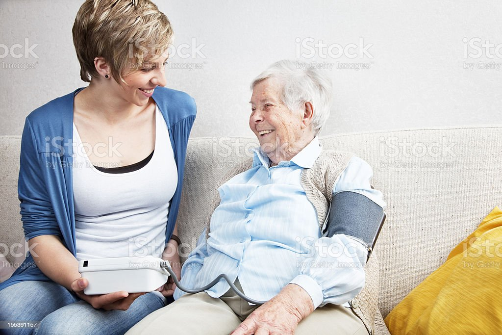 caregiver checking blood pressure senior woman home royalty-free stock photo