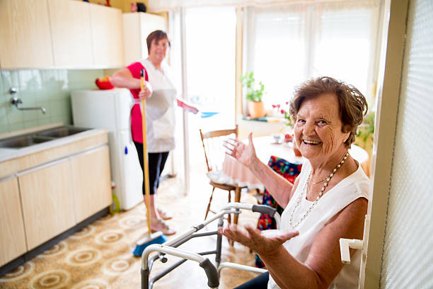 caregiver doing the chores - senior housing stock photos and pictures