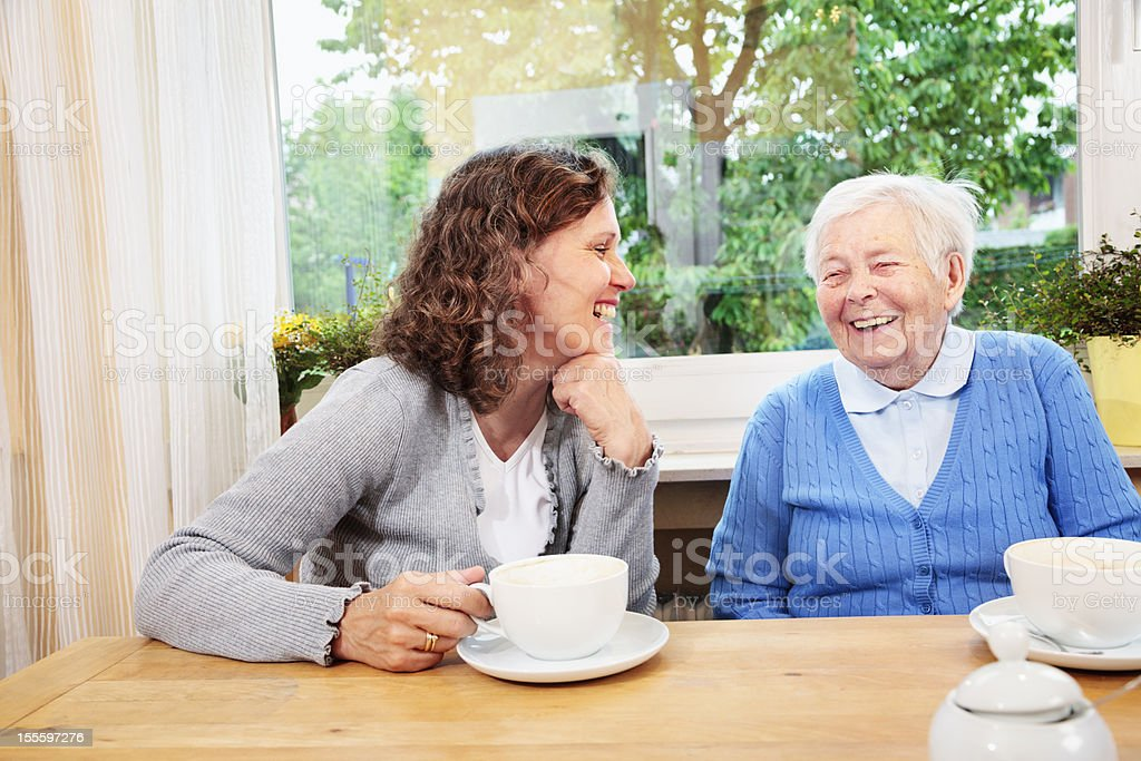 Caregiver drinking coffee with a senior woman stock photo
