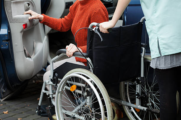 Caregiver helping get into the car Caregiver helping disabled lady get into the car persons with disabilities stock pictures, royalty-free photos & images