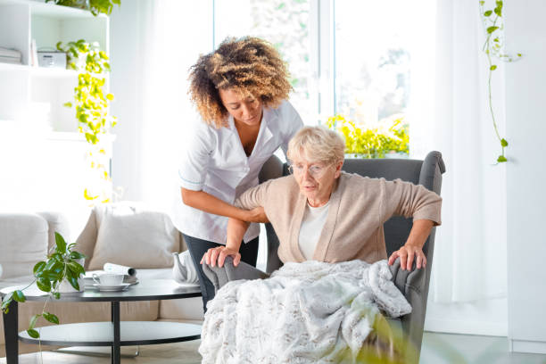 Caregiver helping older lady to stand up stock photo