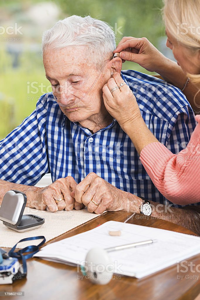 Caregiver helping senior man adjust his hearing aid royalty-free stock photo