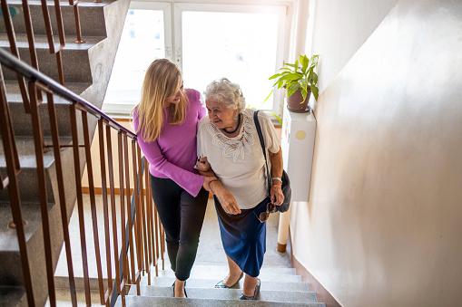 Caregiver helping senior woman climb staircase