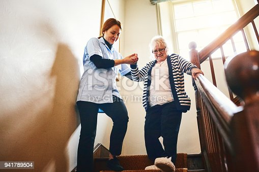 istock Caregiver helping senior woman walking down stairs 941789504