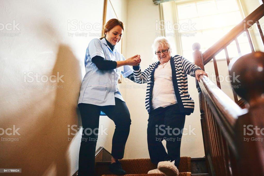 Cuidador de ayuda a mujer senior bajar escaleras - foto de stock